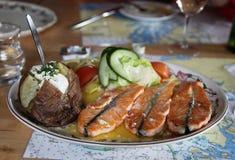 传统冰岛盘用鲑鱼排和被烘烤的土豆和菜 库存图片