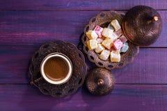传统土耳其咖啡和土耳其快乐糖在黑暗的紫罗兰色木背景 平的位置 库存图片