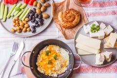 传统土耳其早餐-荷包蛋、新鲜蔬菜、橄榄、乳酪、蛋糕和茶 免版税库存照片