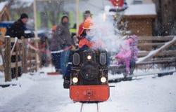 传统圣诞节市场在下斯特滕和儿童驱动的蒸汽路轨由一个小组的组员年轻消防队员 免版税库存图片