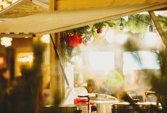 传统圣诞节摊位在与光,装饰,大桶的新年和圣诞节市场上用热的茶,加香料的热葡萄酒 免版税库存照片