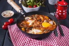 传统墨西哥盘Huevos rancheros -与蕃茄辣调味汁的炒蛋,用炸玉米饼玉米粉薄烙饼、新鲜蔬菜和荷兰芹 免版税库存图片