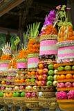 传统巴厘语礼仪寺庙奉献物:大果子和米金字塔在用花装饰的金黄板材 图库摄影