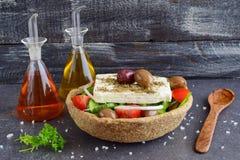 传统希腊沙拉用黄瓜,葱、蕃茄、paptika、希腊白软干酪、橄榄油和牛至在一粒可食用的黑麦滚保龄球 库存照片