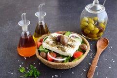 传统希腊沙拉用黄瓜,葱、蕃茄、paptika、希腊白软干酪、橄榄油和牛至在一粒可食用的黑麦滚保龄球 图库摄影