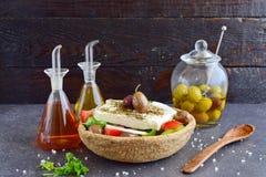 传统希腊沙拉用黄瓜,葱、蕃茄、paptika、希腊白软干酪、橄榄油和牛至在一粒可食用的黑麦滚保龄球 免版税库存照片