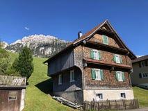 传统建筑学和农舍在Wagital或Waegital谷和由高山湖瓦吉塔莱尔湖Waegitalersee 免版税库存照片