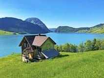 传统建筑学和农舍在Wagital或Waegital谷和由高山湖瓦吉塔莱尔湖Waegitalersee 库存照片