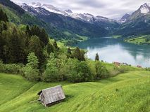 传统建筑学和农舍在Wagital或Waegital谷和由高山湖瓦吉塔莱尔湖Waegitalersee 库存图片