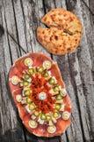 传统开胃菜美味盘Meze和在老被风化的松林野餐桌上的被发酵的皮塔小面包干被撕毁的大面包集合 免版税库存图片