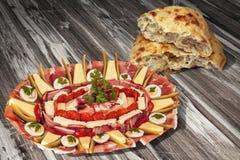 传统开胃菜美味盘Meze和在老被风化的松林野餐桌上的被发酵的皮塔小面包干被撕毁的大面包集合 库存照片