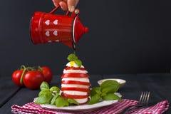 传统意大利人Caprese沙拉-切的蕃茄、无盐干酪乳酪和蓬蒿在黑暗的背景,关闭  Caprese沙拉, 库存照片