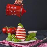传统意大利人Caprese沙拉-切的蕃茄、无盐干酪乳酪和蓬蒿在黑暗的背景,关闭  Caprese沙拉, 库存图片