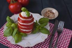 传统意大利人Caprese沙拉-切的蕃茄、无盐干酪乳酪和蓬蒿,黑暗的背景,顶视图, copyspace Caprese 免版税库存照片