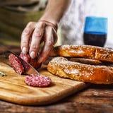传统意大利红葡萄酒,蒜味咸腊肠,迷迭香,面包 关闭人` s手切开了在厨房板的蒜味咸腊肠 免版税库存照片