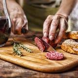 传统意大利红葡萄酒,蒜味咸腊肠,迷迭香,面包 关闭人` s手切开了在厨房板的蒜味咸腊肠 库存图片