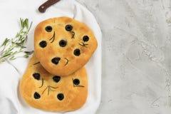 传统意大利语Focaccia用黑橄榄和迷迭香-自创平的面包focaccia 库存照片