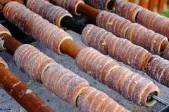 传统捷克食物` Trdelnik ` 在游人中的一个名菜准备的在热的煤炭的木串 库存图片