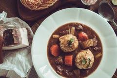 传统斯堪的纳维亚鹿肉炖煮的食物用烟肉和葱Dumpl 图库摄影