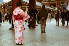 传统日本妇女在摆在Senso籍寺庙,浅草,东京,日本入口的和服穿戴了  免版税图库摄影