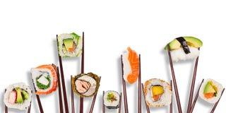 传统日本寿司片被安置在筷子之间,被分离在白色背景 库存照片