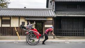 传统日本推车手在有采取在电话的快乐的游人的奈良拉扯了人力车照片selfi 库存照片
