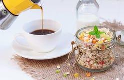 传统早餐新近地煮的咖啡,在一个瓶子的格兰诺拉麦片用薄菏,咖啡罐,杯子,烘干了果子,脯 免版税图库摄影
