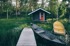 传统木小屋 在湖和码头的芬兰蒸汽浴有渔船的 免版税库存照片