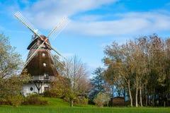 传统木风车在一个繁茂花园里 免版税库存图片