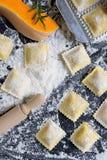 传统未加工的馄饨用在一张木桌上的南瓜用面粉,手工制造,烹饪过程 免版税图库摄影
