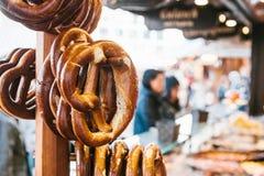 传统椒盐脆饼叫在立场的Brezel吊以被弄脏的街市和人为背景  免版税库存照片