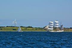 传统横帆高船和现代两桅的游艇海上在绿色海滨前面与领域和风力sta 免版税库存图片