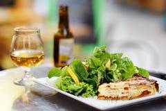 传统法国食物:乳蛋饼洛林和有杯的新鲜的沙拉叶子在背景的啤酒 免版税库存照片