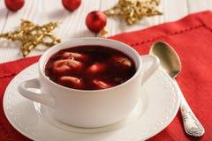 传统波兰圣诞节汤-红色罗宋汤汤用在白色板材的饺子 库存照片
