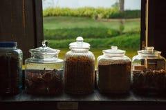 传统泰语烘干了在玻璃瓶子存放的医药,自然草本分类在架子在木窗口旁边 医学东方人 库存图片