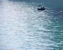 传统渔夫小船和海景与光反射在水背景 免版税库存图片