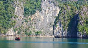 传统渔夫小船和海景在水和海岛背景,下龙湾,越南 库存照片