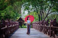传统礼服服装红色伞的美丽的泰国女孩  免版税库存图片