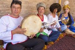 传统礼服的Khorezmian音乐家演奏并且唱地方歌曲 库存照片
