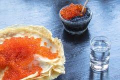 传统稀薄的俄国薄煎饼用在黑暗的土气木背景的红色鱼子酱 免版税库存照片