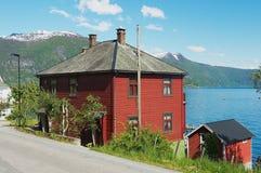 传统红色绘了有Sognefjord的挪威房子在背景在Balestrand,挪威 免版税库存照片