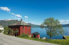 传统红色绘了有Sognefjord的挪威房子在背景在Balestrand,挪威 免版税库存图片
