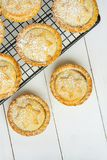 传统英国家庭焙制圣诞节甜的酥皮点心与苹果计算机填装在冷却的机架顶视图的葡萄干坚果的肉馅饼 免版税库存照片