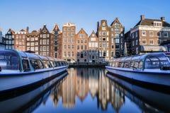 传统荷兰房子和旅游运河船的反射 免版税库存照片