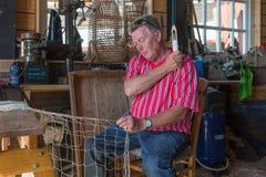 传统荷兰服装修补工作捕鱼网的人在车间 免版税库存照片