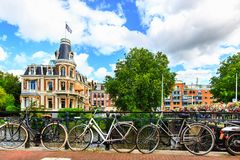 传统荷兰自行车沿街道停放了在运河的Museumbrug桥梁 阿姆斯特丹在夏天,荷兰,欧洲 库存图片