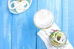 传统荷兰语用了卤汁泡鲱鱼用柠檬和葱在瓶子 在玻璃的新鲜的比利时啤酒 在蓝色背景的海鲜 免版税库存照片