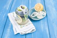 传统荷兰语用了卤汁泡鲱鱼用柠檬和葱在瓶子 在蓝色背景的海鲜 复制空间 库存图片