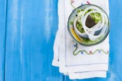 传统荷兰语用了卤汁泡鲱鱼用柠檬和葱在瓶子 在蓝色背景的海鲜 复制空间 免版税库存图片