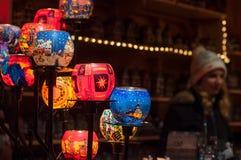 传统蜡烛特写镜头在与被弄脏的妇女的圣诞节市场上背景的 免版税库存照片